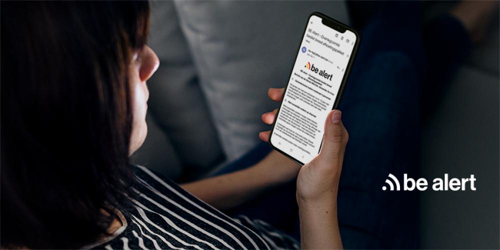 Frau, die eine Be-Alert-Nachricht auf ihrem Handy liest