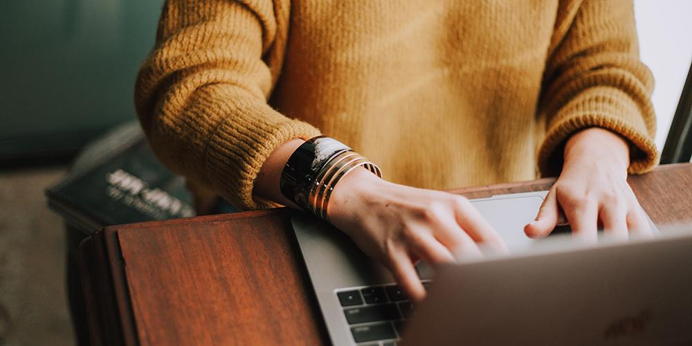 Frau, die etwas auf einem Laptop tippt